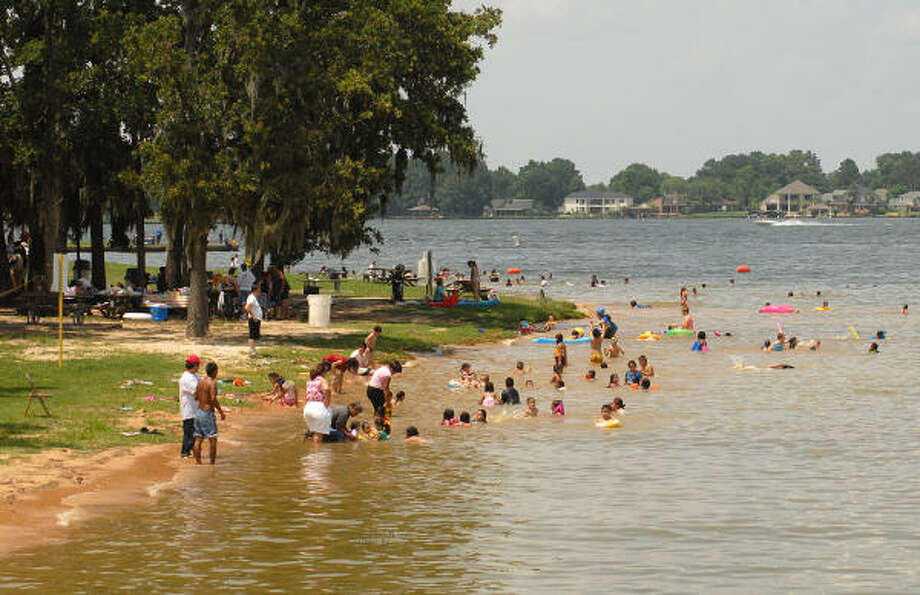 Visitors at Lake Conroe Park enjoy the water and the shade trees. The beach area had no water after the lake level was lowered to repair the dam for damage caused by Hurrican Rita in 2005. Activity on Lake Conroe has increased this summer as the water level is back to its normal depth. Photo: David Hopper, For The Chronicle