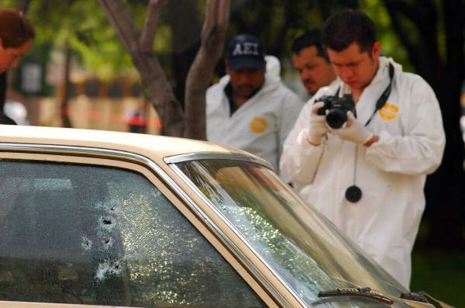 Forensics investigators check a car at a shooting scene Tuesday near Monterrey, Mexico. Gunmen opened fire on the police headquarters, wounding five people, officials said. Photo: MONICA RUEDA, Ap