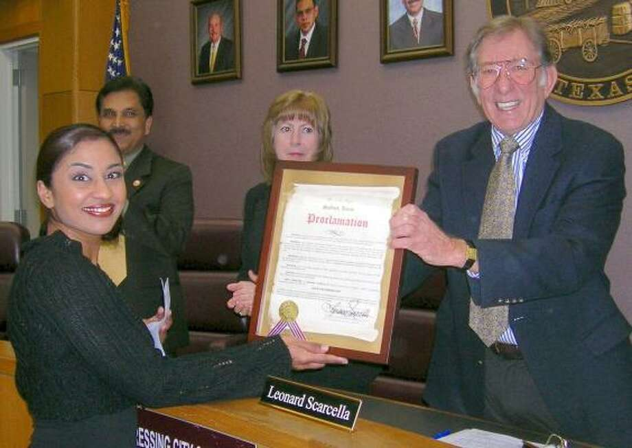Stafford Mayor Leonard Scarcella presents a proclamation honoring Julie Zachariah on her three tours of duty in Iraq during the Wednesday night City Council meeting. Photo: SESHADRI KUMAR, For The Chronicle