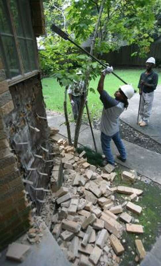 Thomas Alarosa, with Klassic Hardwood Floors, breaks away bricks from a home in the 5500 block of Chaucer on Friday. The materials will be salvaged for use in Rice University's new child care center. Photo: STEVE CAMPBELL, CHRONICLE