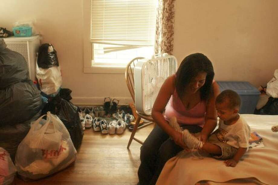 Lisa Rivera, shown with her infant son Celeb, shares a room with her four children at Jessie's House in Amherst, Mass. Photo: NATHAN K. MARTIN, AP