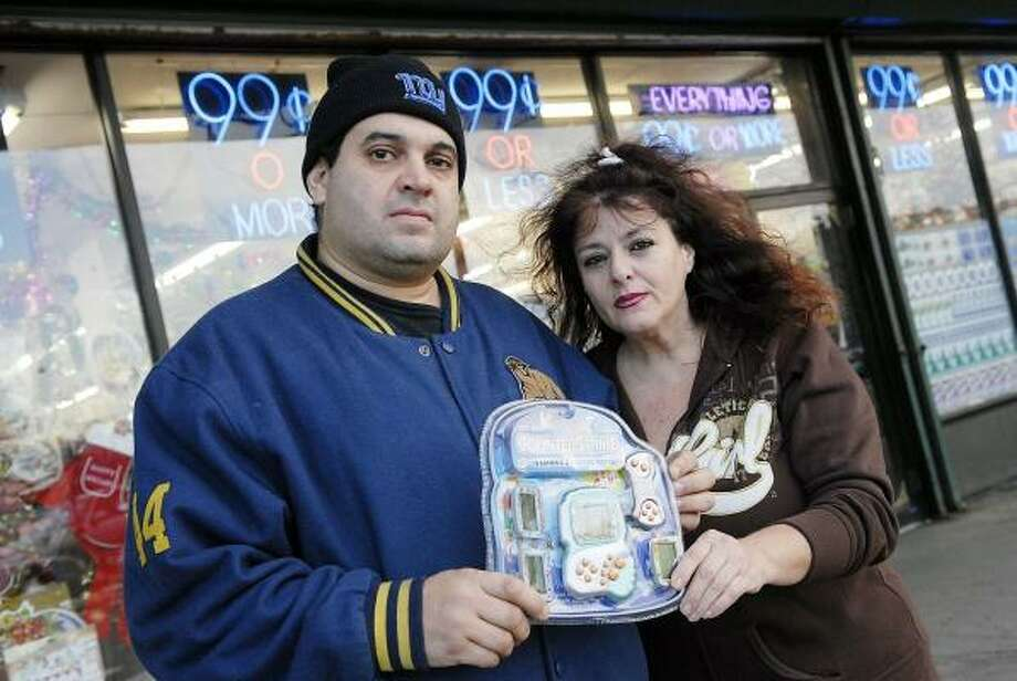 """Carl Cappi and Maryanne Russell hold a copy of the game being sold in the store. Russell said, """"My first reaction was to say, 'What are you guys, crazy?' That should not be a joke or game."""" Photo: REENA ROSE SIBAYAN, JERSEY JOURNAL"""