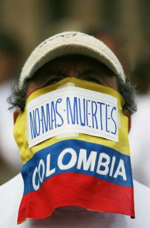 "A man, with his face covered with a sign reading in Spanish ""No more death,"" takes part in a march to demand the release of the country's kidnapped people, in Bogota, Colombia, July 5. Photo: William Fernando Martinez, AP"