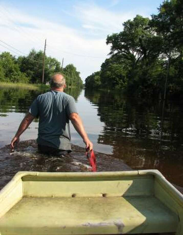 Joe Morris pulls his boat down Powell Road in Trinity's Deep River Plantation subdivision on Monday. Morris and his wife headed deep into the subdivision to check on the home of a relative. Photo: ROBBIE BYRD, THE HUNTSVILLE ITEM