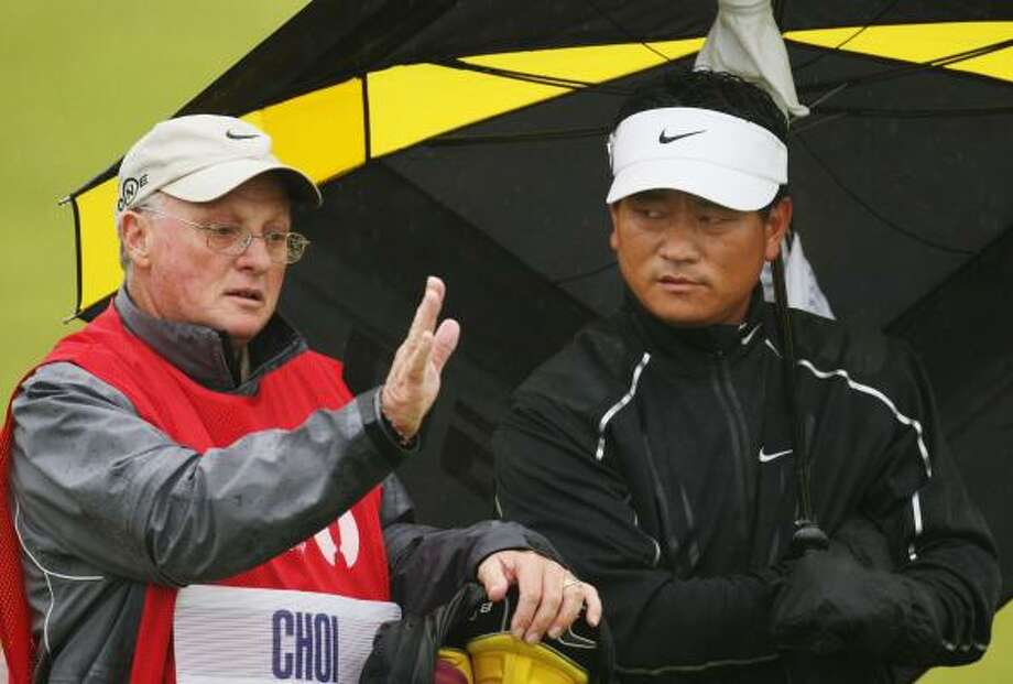 K.J. Choi, right, listens to caddie Andy Prodger during the first round. Choi shot 69. Photo: Ross Kinnaird, Getty Images