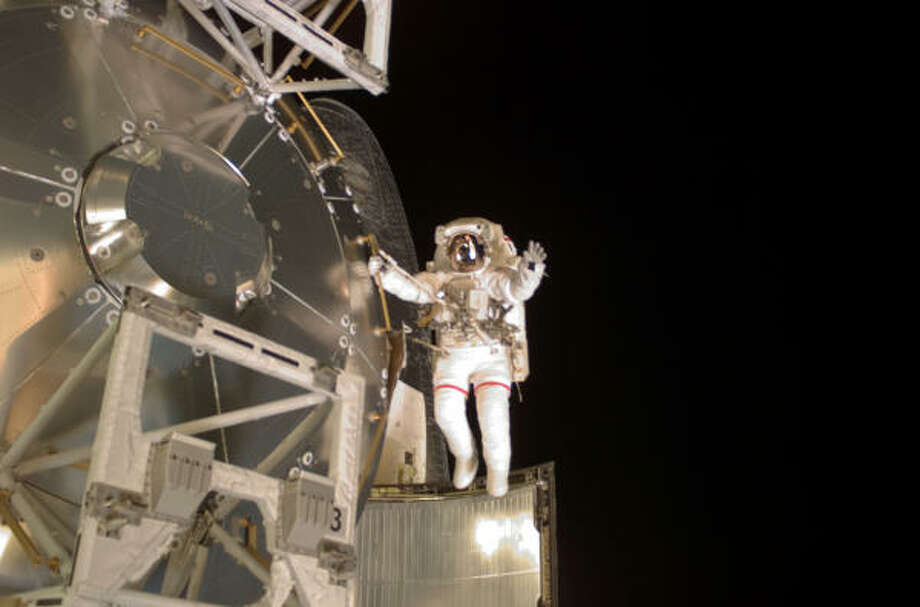 Astronaut Rex Walheim holds onto a handrail on the Columbus laboratory and spreads his arms Friday. The shuttle could be ready to land by Wednesday. Photo: NASA