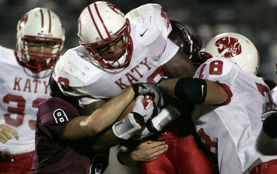 Katy running back Aundre Dean pushes his way through a pile of A&M Consolidated defenders with the help of teammate Eric Bell. Photo: Paul Zoeller