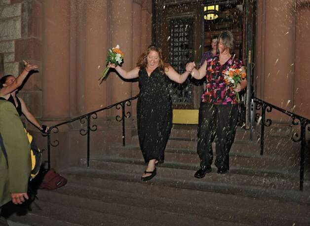Beth Relyea, left, and Joanne Trinkle exit City Hall in Albany, N.Y. after being one of the first same-sex couples to marry in New York State on Sunday, July 24, 2011.  (Lori Van Buren / Times Union) Photo: Lori Van Buren