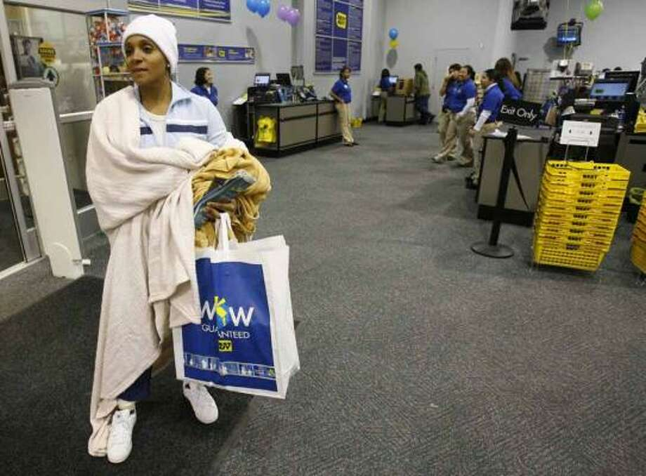 "Rhonda Jones, of Houston, waits for her family to finish shopping during ""Black Friday"" at Best Buy, 13238 Northwest Freeway, on Friday in Houston. She was the first to check out shortly after the store opened at 5 a.m. She had waited in line outside the store since 11:30 p.m. Thursday. Photo: Melissa Phillip, Chronicle"