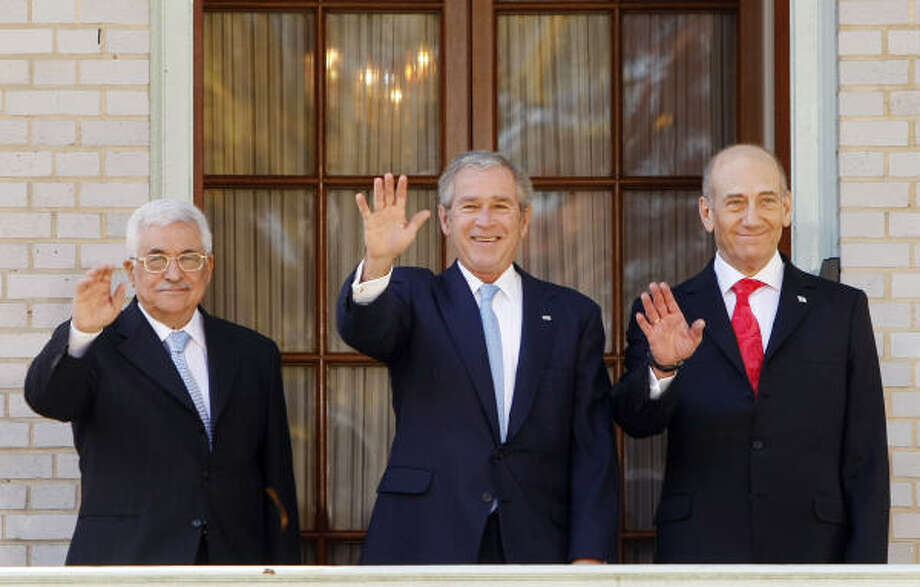 President Bush, flanked by Israeli Prime Minister Ehud Olmert, right, and Palestinian President Mahmoud Abbas, left, waves prior to the start of the Middle East peace summit. Photo: Gerald Herbert, AP