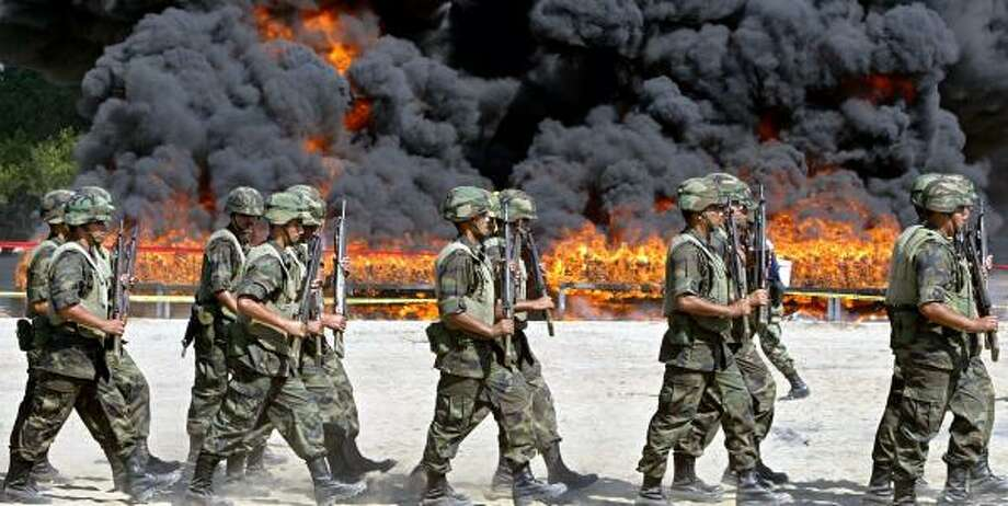 Mexican soldiers march to the site of the incineration of 23.5 tons of cocaine. The haul is part of a crackdown by President Felipe Calderon against powerful drug lords. Photo: ALFREDO ESTRELLA, AFP/GETTY IMAGES