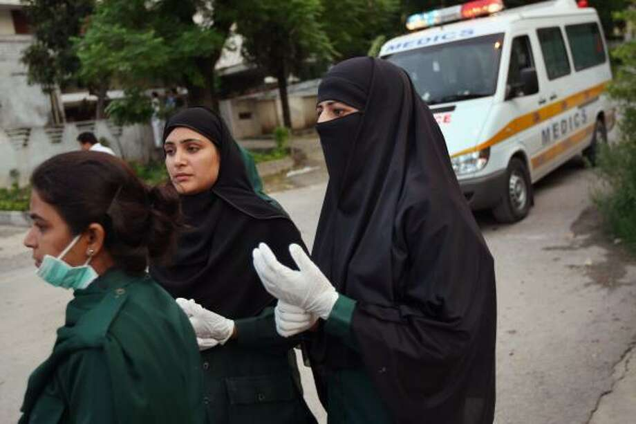 Paramedics head to the bombing site in Islamabad, Pakistan, on Sunday, a year after a military operation at the Red Mosque. Photo: JOHN MOORE, GETTY IMAGES