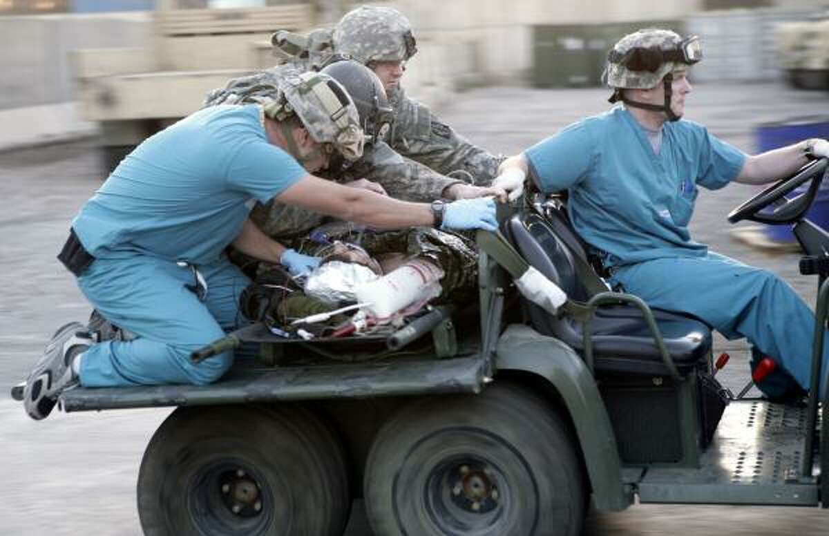Army medics rush a wounded civilian contractor to the emergency room at Ibn Sina Hospital in the Green Zone of Baghdad in this Dec. 9 photo. Houston-based KBR, the Pentagon's largest contractor in Iraq, escaped the worst of the carnage.