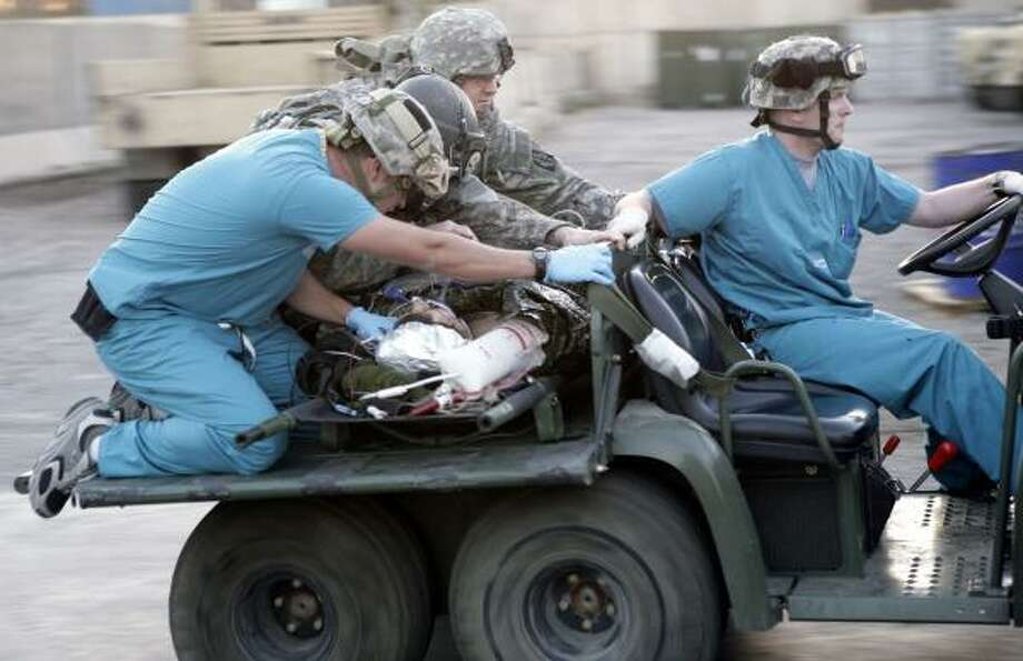 Army medics rush a wounded civilian contractor to the emergency room at Ibn Sina Hospital in the Green Zone of Baghdad in this Dec. 9 photo. Houston-based KBR, the Pentagon's largest contractor in Iraq, escaped the worst of the carnage. Photo: MAYA ALLERUZZO, ASSOCIATED PRESS FILE
