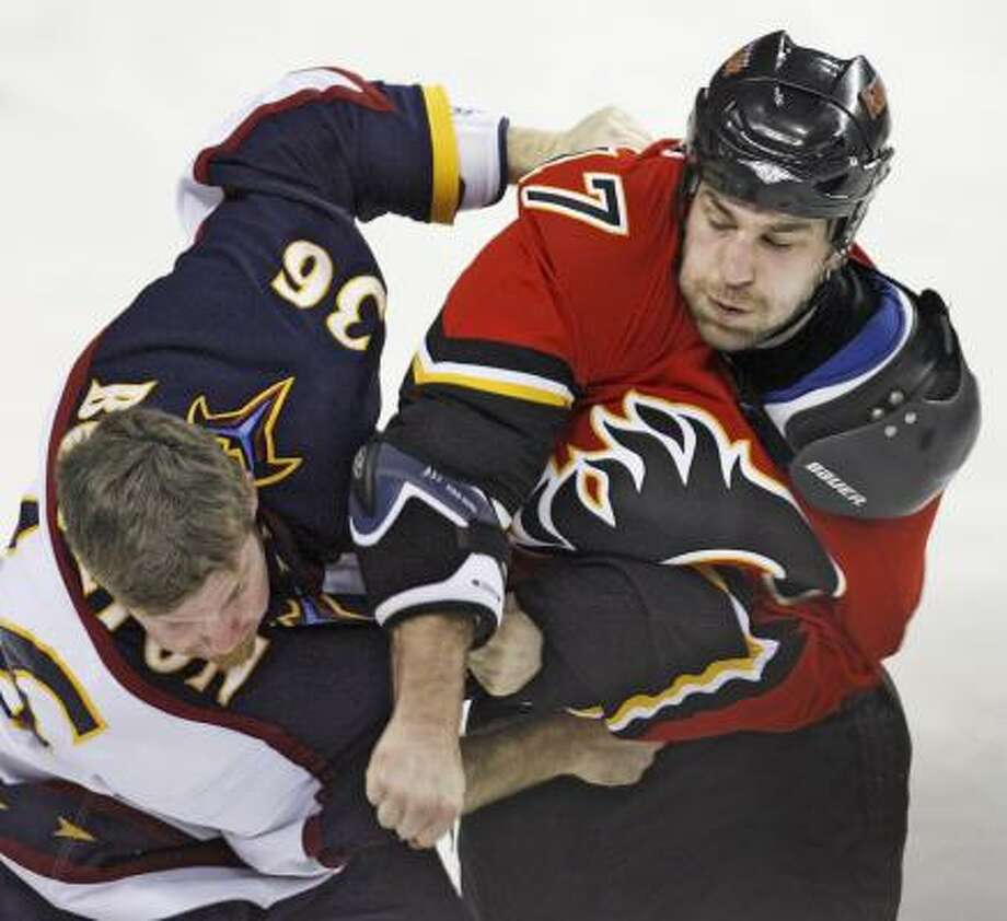 Atlanta's Eric Boulton, left, takes on Calgary's Eric Goddard in the first period. Each player drew five minutes for fighting. Photo: Jeff McIntosh, AP