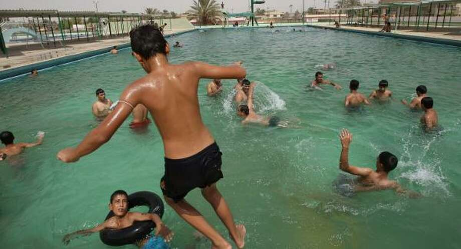 An Iraqi youth jumps into the re-inaugurated Al-Asafah pool complex in Baghdad's Beida district on Thursday. Part of the complex had been used to recruit extremists, a U.S. Army spokesman said. Photo: ALI AL-SAADI, AFP/GETTY IMAGES