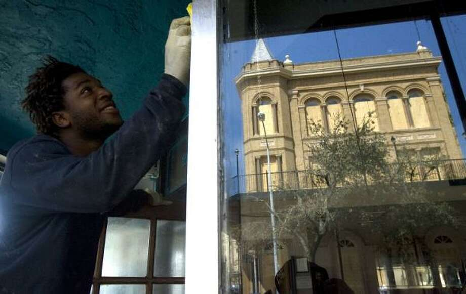 Steven Frasier, a contract worker from Georgia, on Thursday cleans windows of the Stork Club in Galveston, where officials are trying to keep evacuees from returning. Photo: JOHNNY HANSON, CHRONICLE
