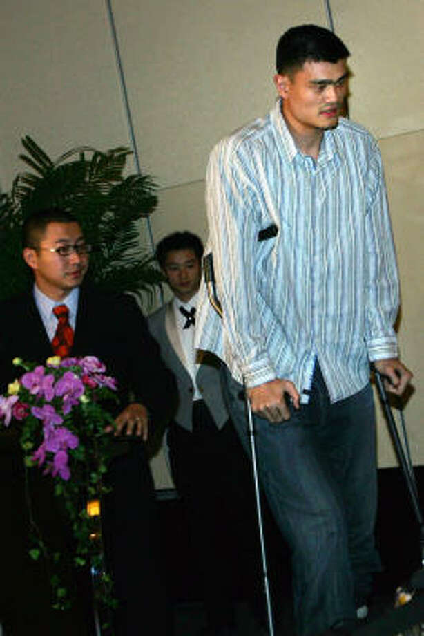 Yao Ming walks on crutches as he arrives for a news conference about the Olympics and his foot injury Friday in Beijing. Yao will try the therapeutic method of Chinese medicine for his foot injury after returning to China on Thursday. Photo: Feng Li, Getty Images