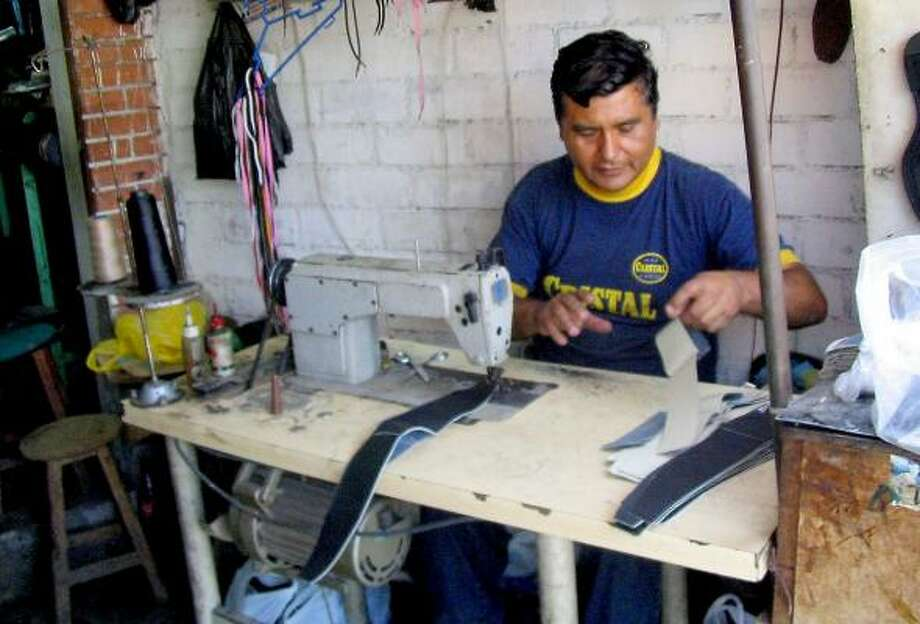 Wilmer Pinto works at his sewing machine in his Lima, Peru, workshop. He is one of millions working in Latin America's informal economy. Photo: TYLER BRIDGES, MIAMI HERALD