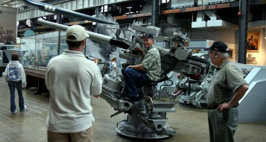 Stan Richins of California tries sitting in a gun seat at the Navy museum in Washington, D.C. Military museums are working to attract Americans who have grown accustomed to being entertained. Photo: SUSAN BIDDLE, WASHINGTON POST