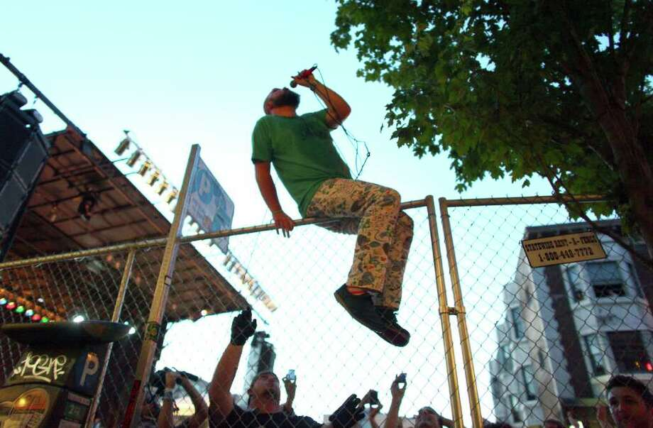 Les Savy Fav lead singer Tim Harrington sings while straddling a fence after scaling it during day two of the Capitol Hill Block Party on Saturday, July 23, 2011. Harrington, known for his wild acts onstage, then tossed his microphone into the open window of a second story apartment, climbed the stairs and performed there, high over the crowd. Photo: JOSHUA TRUJILLO / SEATTLEPI.COM