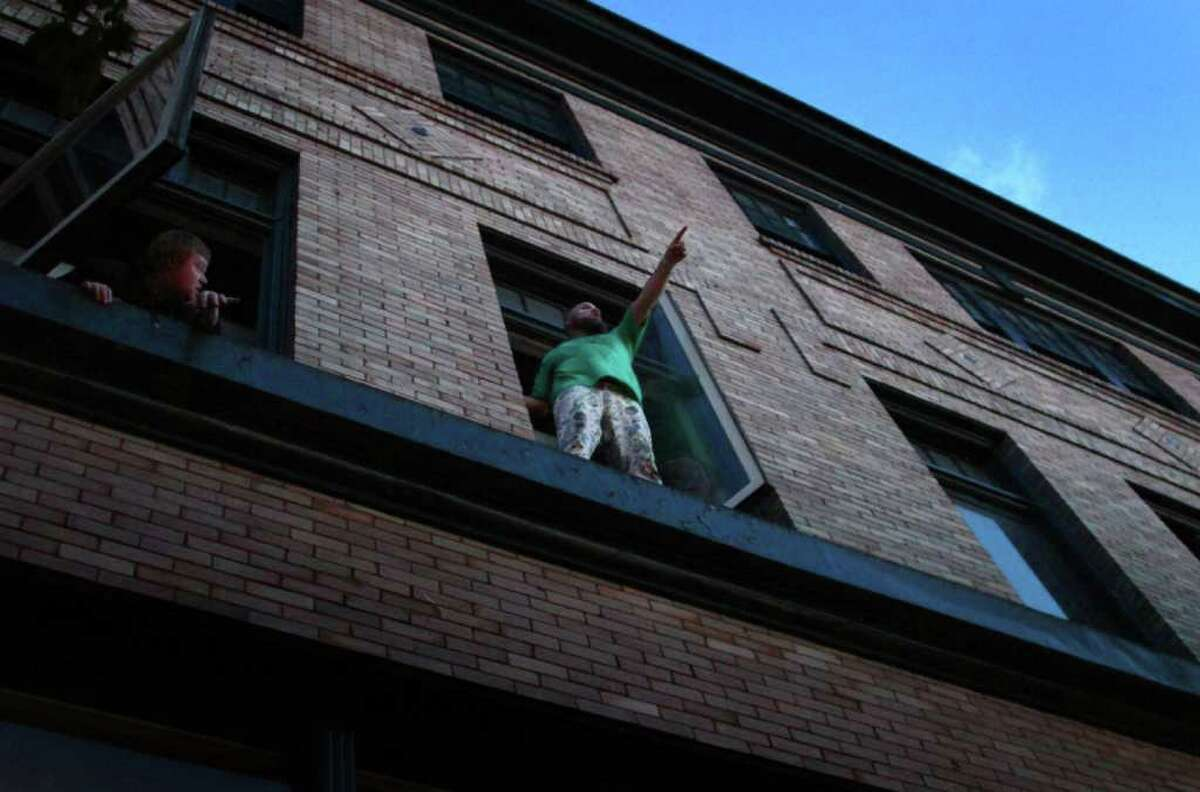 Les Savy Fav lead singer Tim Harrington performs in an apartment window, high over the crowd on day two of the Capitol Hill Block Party.