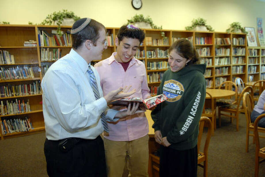 Rabbi Ari Segal, left, meets with students Noah Jackson, 16, and Deena Perl, 15, in the library at the Robert M. Beren Academy, 11333 Cliffwood Drive. Photo: Kim Christensen, For The Chronicle