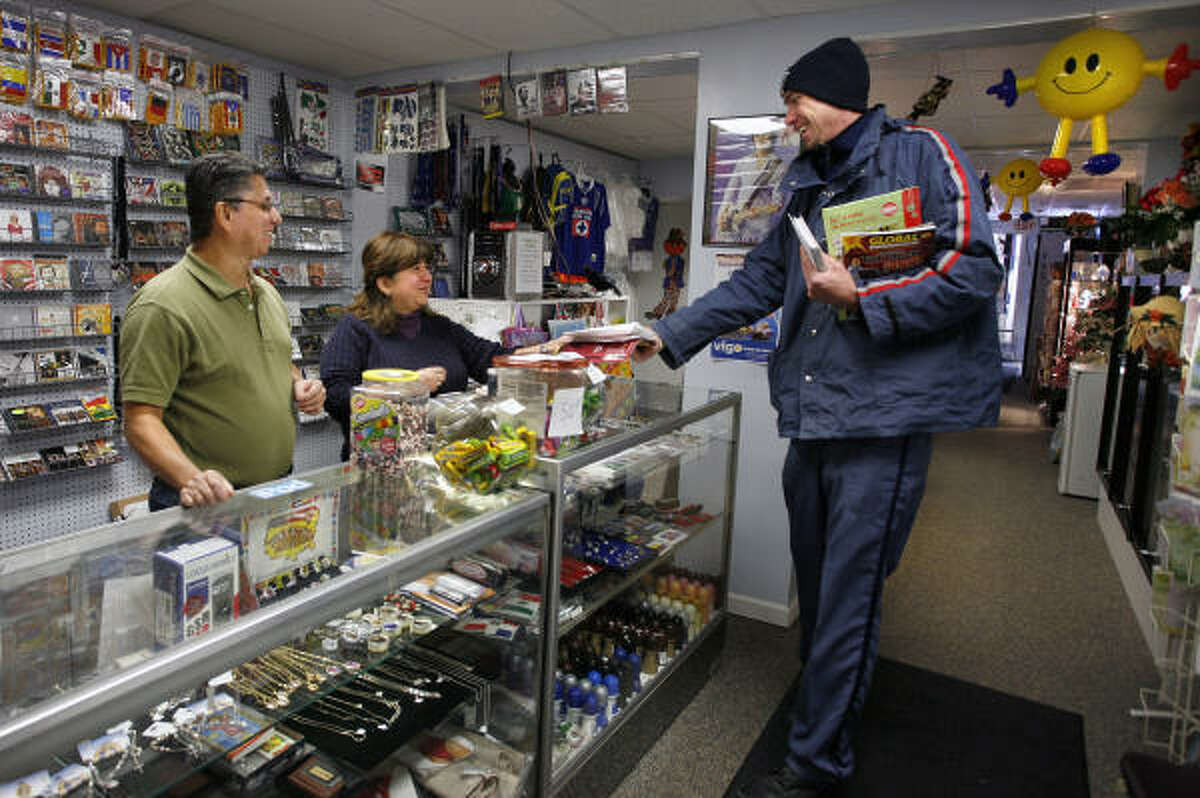 Mail carrier Jake Saylor visits with Oscar, left, and Isabel Rubio, owners of Isabel's Gift Shop in downtown Hazleton, Pa. The Rubios say they have dipped into savings to stay open.