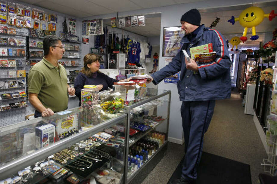 Mail carrier Jake Saylor visits with Oscar, left, and Isabel Rubio, owners of Isabel's Gift Shop in downtown Hazleton, Pa. The Rubios say they have dipped into savings to stay open. Photo: STEVE KLAVER, AP