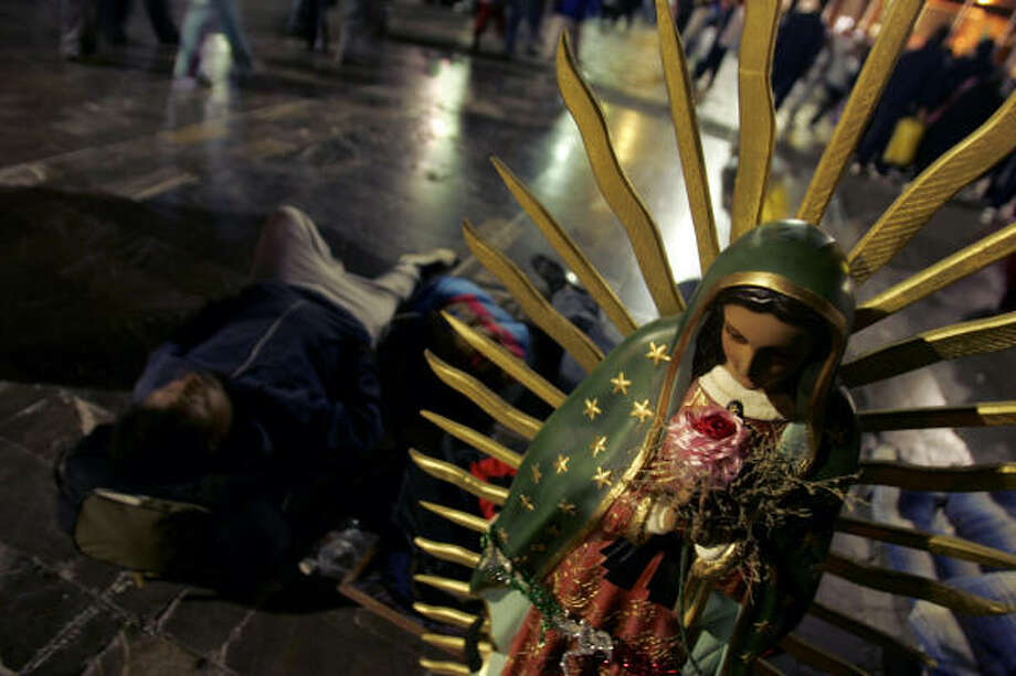 Mexican pilgrims sleep before the image of the Virgin of Guadalupe during annual celebrations Monday in Mexico City. The festivities mark the 475th anniversary of the Virgin's appearance before Indian peasant Juan Diego in 1531. Photo: ALFREDO ESTRELLA, AFP/Getty Images