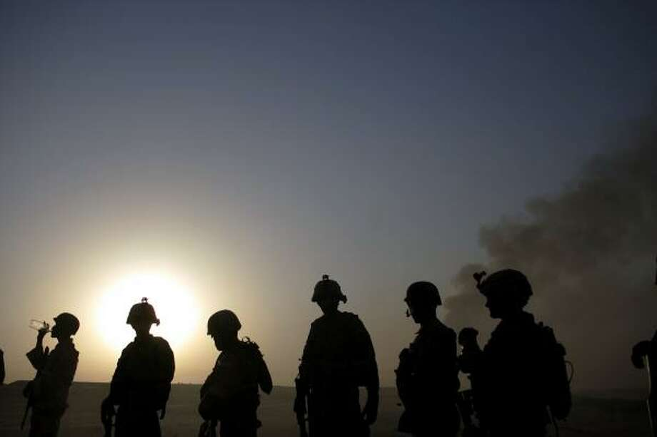 Iraqi army soldiers, accompanied by U.S. Army soldiers, walk down a field as plumes of smoke rise from a burned irrigation canal outside Balad Ruiz. The soldiers were searching for weapons caches. Photo: MARKO DROBNJAKOVIC, ASSOCIATED PRESS