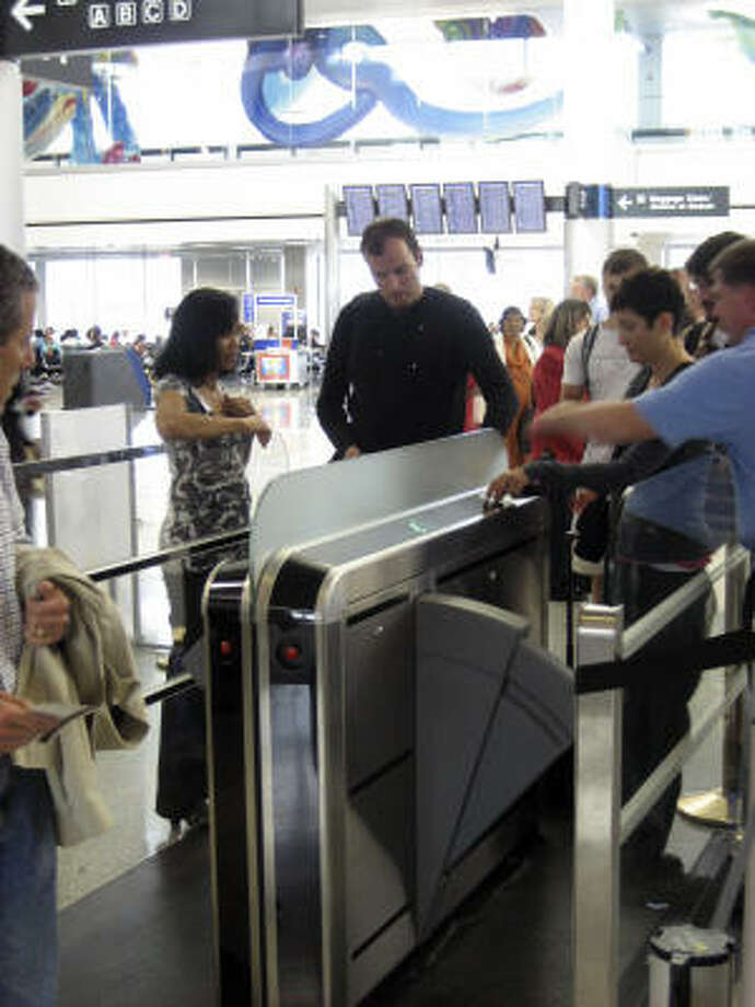 Travelers pass through Continental Airlines' new gates at George Bush Intercontinental Airport.  Continental  is testing the gates, which let travelers board planes without using an agent. Photo: Bloomberg