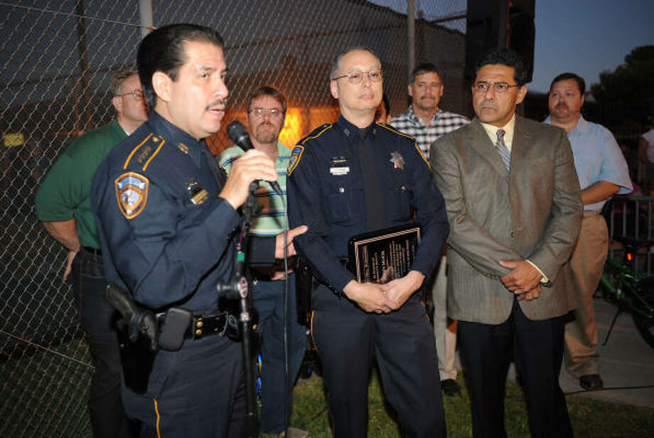 Harris County Sheriff Adrian Garcia, left, along with Maj. Bob Doguim, Homeland Security Bureau, pays tribute to Deputy John Mook for his work leading to the arrest of gang members in the once gang-infested community during National Night Out and Mook Park dedication at Chimney Hills subdivision on Oct. 5. Photo: Thomas Nguyen, For The Chronicle