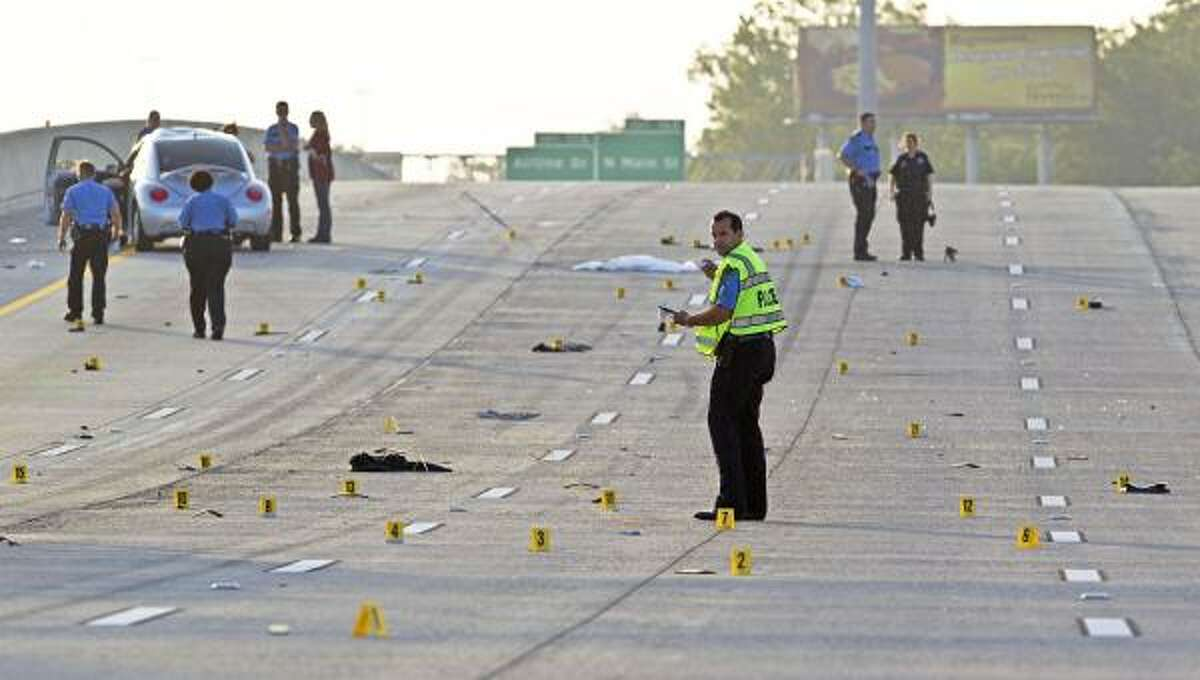 Investigators work at the scene of the tragedy along Loop 610 North.