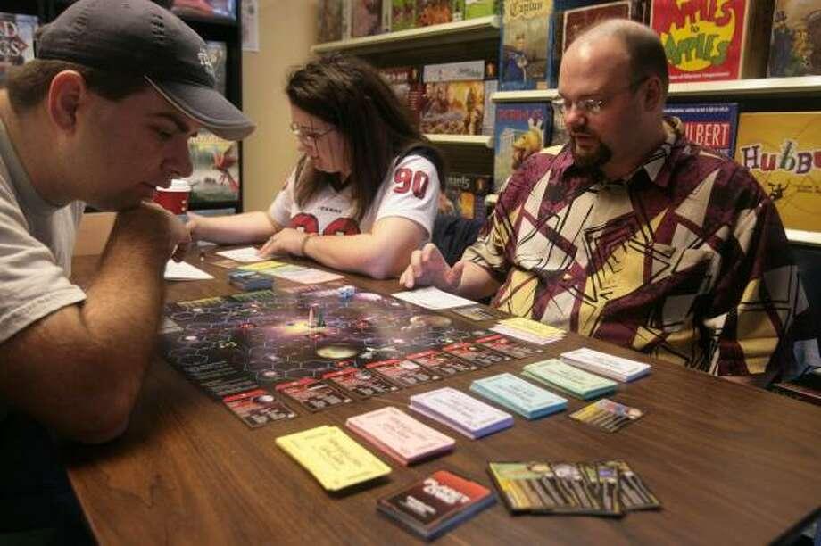 Nathan Abrashoff, left, Shelly Abrashoff and Daniel Strain play a round of Smugglers of the Galaxy at Midnight Comics & Games. Photo: MAYRA BELTRAN, CHRONICLE