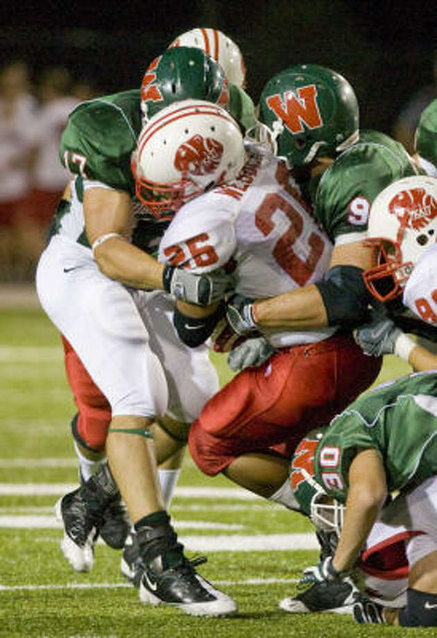 Katy's Michael Webber (26) is thrown for a loss by The Woodlands' Colin Renton (17), Cameron Knight (91 right) and Ryan Cusimano (30) in the first half on Friday at Woodforest Stadium in The Woodlands. Photo: Steve Campbell, Houston Chronicle