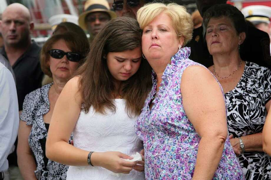 Widow Laurie Baik and her daughter, Margaret, attend a Bridgeport Fire Department Memorial Dedication ceremony honoring firefighter Michel Baik and  Lt. Steven Velasquez on Sunday, July 24, 2011. The firefighters were killed in the line of duty last year.  The ceremony took place at the Engine 7/ Ladder 11 firehouse on Ocean Terrace. Photo: B.K. Angeletti / Connecticut Post
