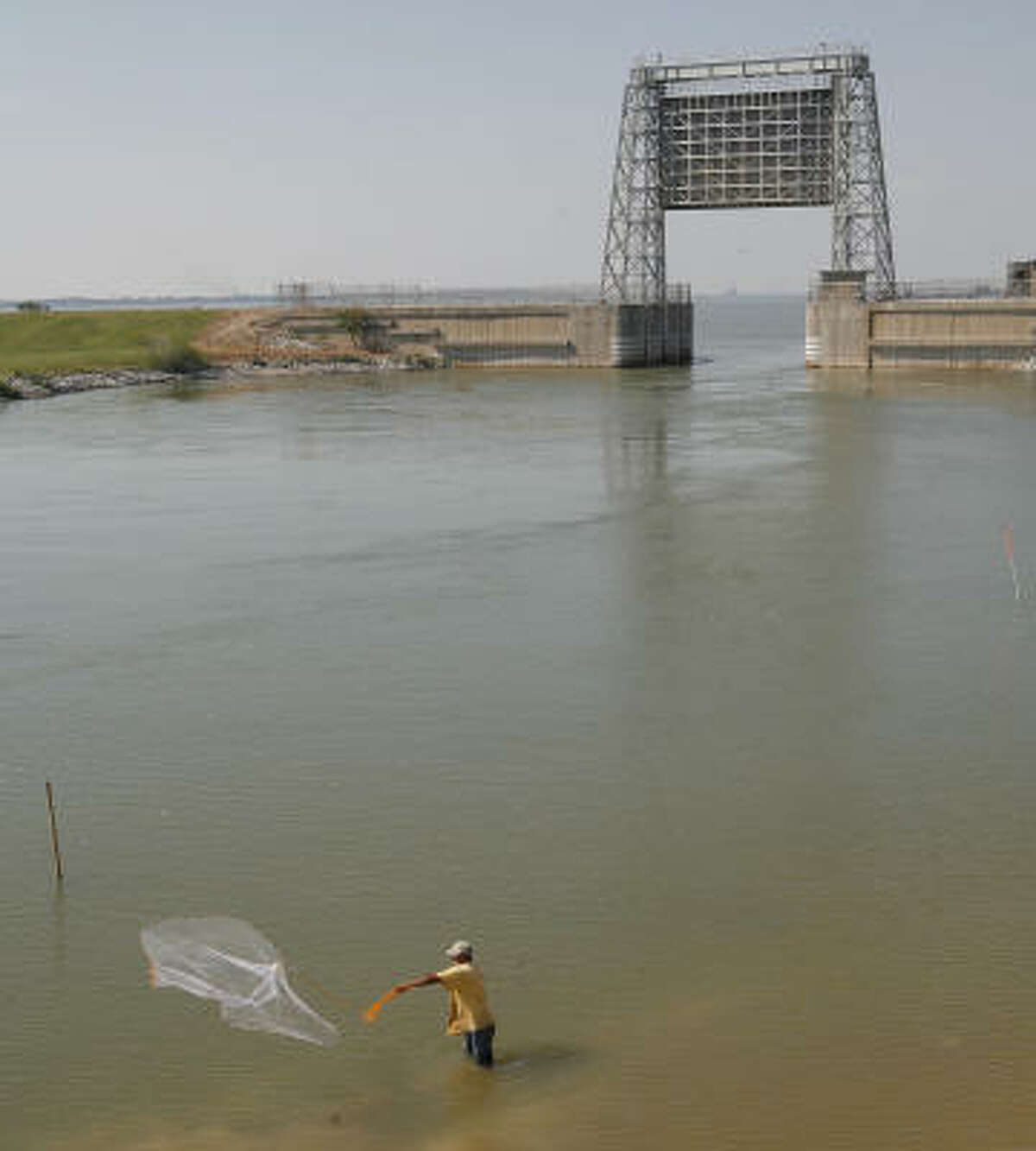 Hector Vasquez fishes with a net in Moses Lake, which is separated from Galveston Bay by the tide gate in the background, part of the Texas City hurricane-levee system.