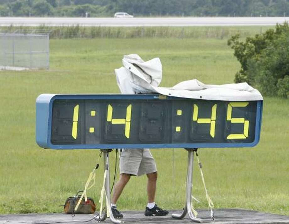 A worker removes a tarp from a countdown clock Thursday at Kennedy Space Center after the space shuttle Atlantis was waved off from landing. Photo: JAMES NIELSEN, CHRONICLE