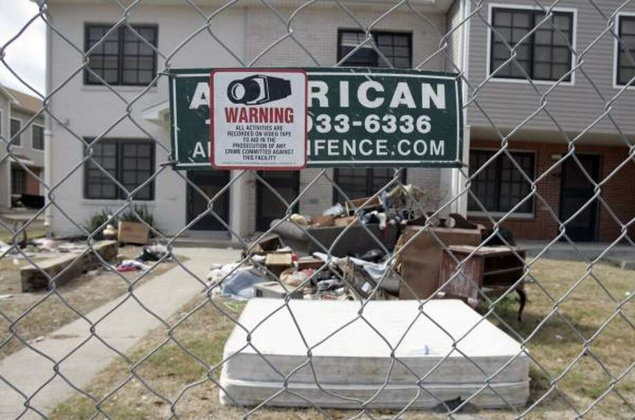 A fence keeping residents out of the Pecan Terrace housing project in Galveston surrounds the property Friday. The residences were damaged during Hurricane Ike. Photo: PAT SULLIVAN, ASSOCIATED PRESS