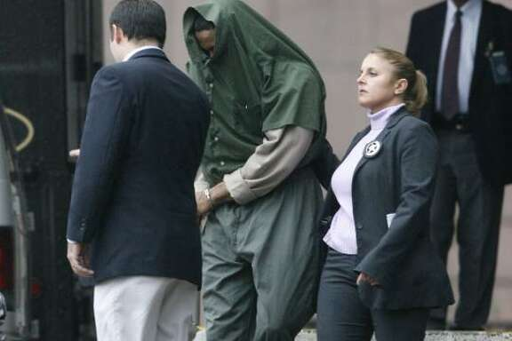 Tyrone Williams is escorted out of the U.S. Courthouse in Houston on Thursday after being sentenced for his role in the 2003 human-smuggling scheme that left 19 illegal immigrants dead.