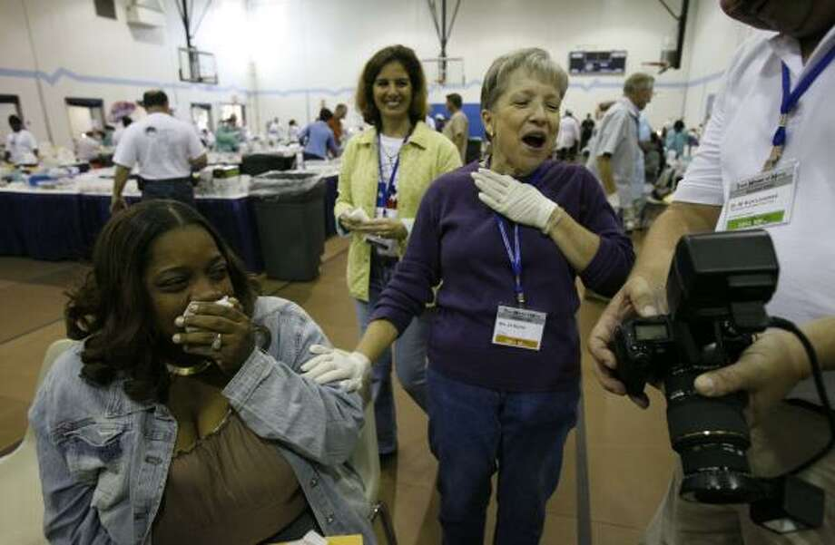 Dental patient Cheryl Cameron, left, cries happy tears as volunteer Jill Boyles, of Alvin, right, reacts to before and after photos of Cameron's teeth Friday at Spring Branch Family Development Center. Photo: MELISSA PHILLIP, CHRONICLE