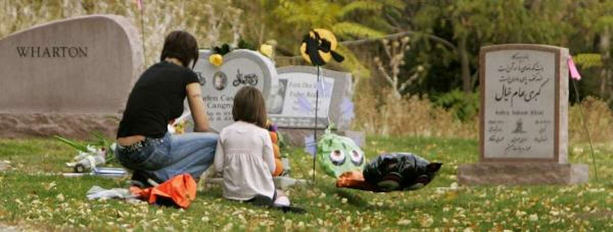 Carly Moore and her daughter, Taylor, 6, visit the grave site of Moore's son, Jayden Cangro, in Salt Lake City. In July 2006, Moore's boyfriend, Phillip Guymon, hurled the 2-year-old across a room because he balked at going to bed. The child died as a result.