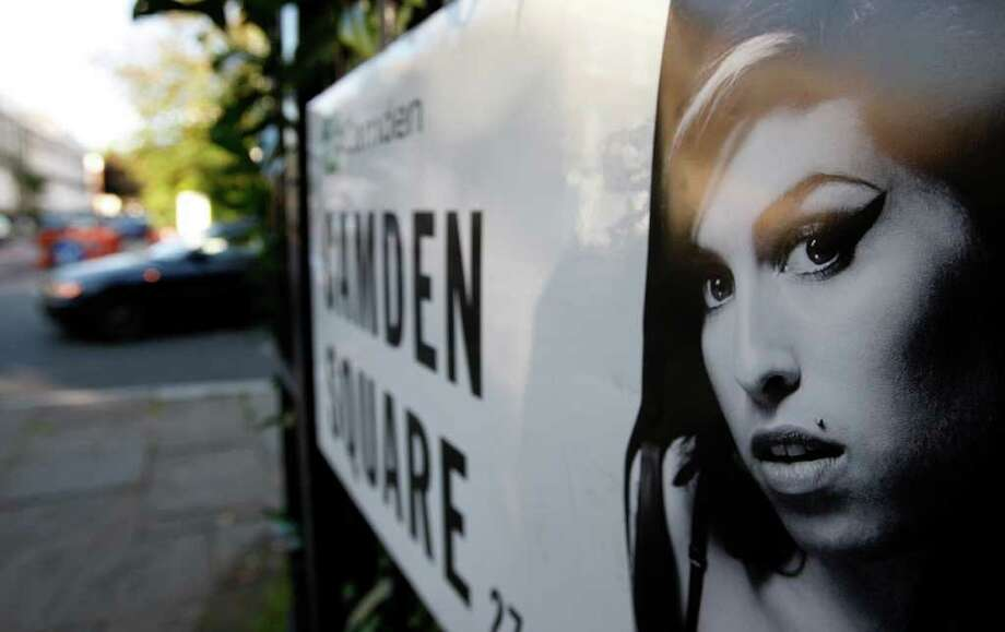 A picture of singer Amy Winehouse is seen stuck to an address sign as a car drives past it near the residence of Winehouse in Camden Square, north London, Sunday, July 24, 2011. Amy Winehouse, the beehived soul-jazz diva whose self-destructive habits overshadowed a distinctive musical talent, was found dead Saturday, July 23, 2011 in her London home. She was 27.(AP Photo/Akira Suemori) Photo: Akira Suemori, STR / AP