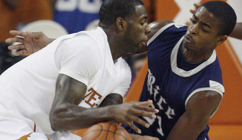 Rice guard Rodney Foster, right, forces a turnover against Texas forward Damion James during the first half. Photo: Harry Cabluck, AP