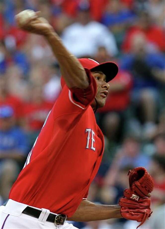 Texas Rangers' Alexi Ogando delivers to the Toronto Blue Jays during the first inning of a baseball game, Sunday, July 24, 2011, in Arlington, Texas. (AP Photo/Tony Gutierrez) Photo: Tony Gutierrez, Associated Press / AP