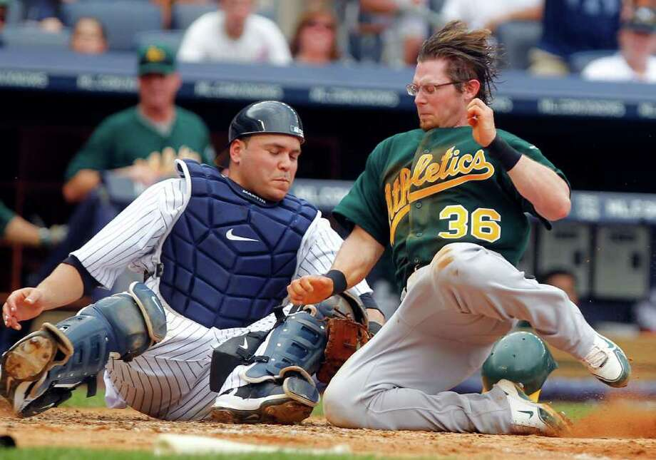 New York Yankees catcher Russell Martin, left, tags out Oakland Athletics' Eric Sogard (36) who was trying to score on a double by Hideki Matsui in the fifth inning of a baseball game at Yankee Stadium in New York, Sunday, July 24, 2011. (AP Photo/Paul J. Bereswill) Photo: Paul J. Bereswill