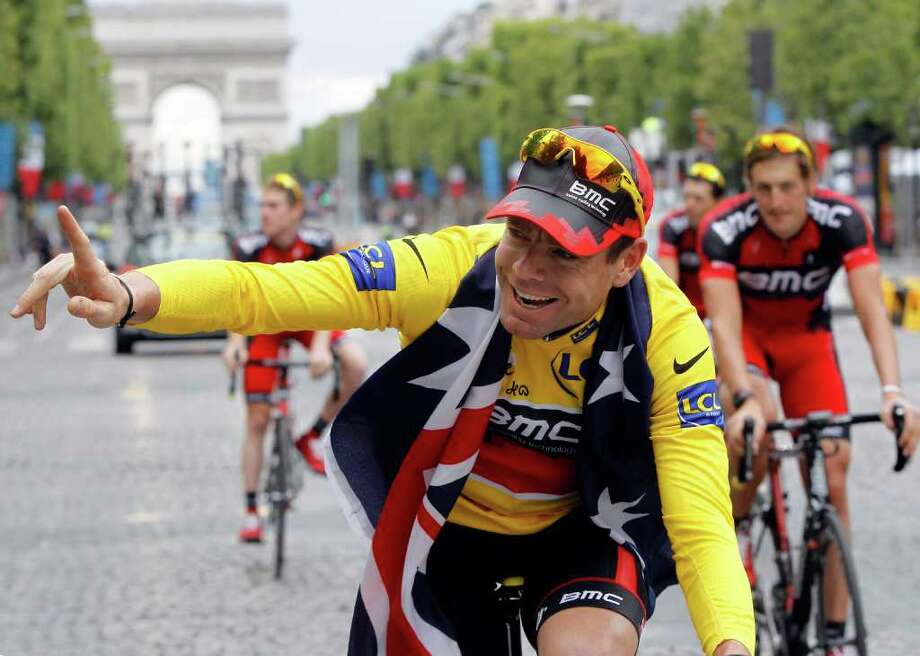 Tour de France winner Cadel Evans of Australia, wearing the overall leader's yellow jersey, cycles down the Champs Elysees during the victory parade after winning the Tour de France cycling race in Paris, France, Sunday July 24, 2011.  (AP Photo/Laurent Cipriani) Photo: Laurent Cipriani