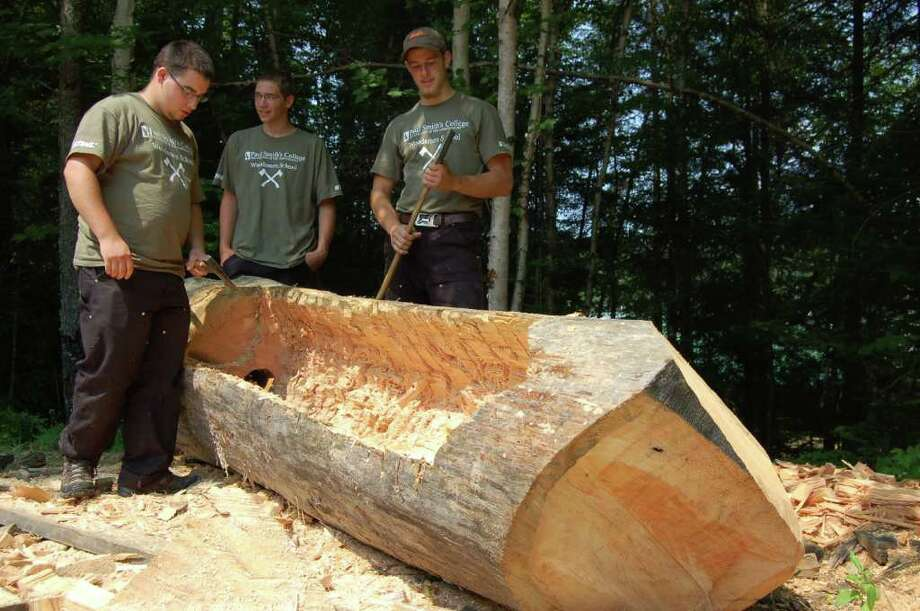 Students are carving out a log to use as a dugout canoe on Tuesday July 19, 2011. The project was part of a lesson at the Adirondack Woodsmen's School at Paul Smith's College.  (Scott Waldman / Times Union) Photo: Scott Waldman