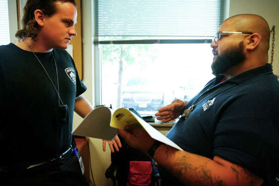 Animal Care Services specialists Joel Skidmore (left) and Joseph Flores discuss a plan of action at the ACS office on Texas 151 for some cases they planned to check out on Thursday, July 7, 2011. Photo: Sally Finneran/sfinneran@express-news.net / sfinneran@express-news.net
